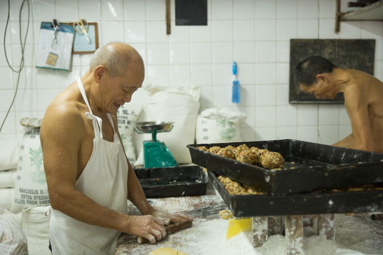 擁有50多年手造中式餅經驗的鐵叔﹙左﹚稱,機製月餅的味道始終不及手造月餅。(李孫彤攝)